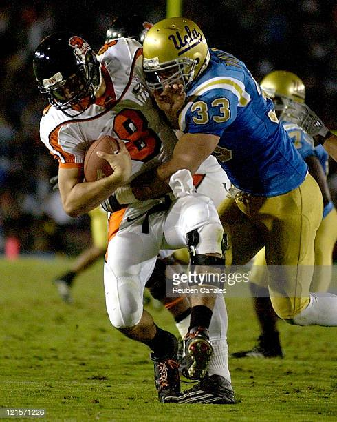 Quarterback Matt Moore of the Oregon State Beavers is sacked by Bruins linebacker Christian Taylor in a 25 to 7 loss to the UCLA Bruins on November...