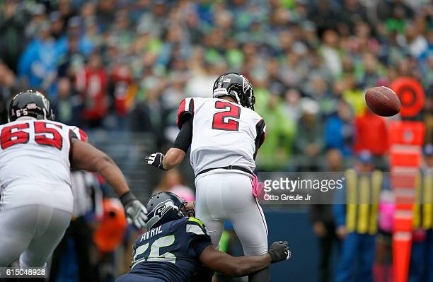 Quarterback Matt Ryan of the Atlanta Falcons fumbles the ball against the defense of defensive end Cliff Avril of the Seattle Seahawks at CenturyLink...