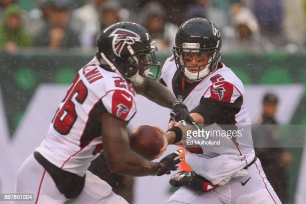 Quarterback Matt Ryan of the Atlanta Falcons hands the ball off to teammate running back Tevin Coleman against the New York Jets during the second...