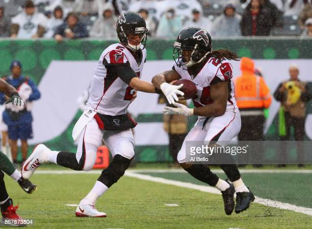 Quarterback Matt Ryan of the Atlanta Falcons handsoff the ball to teammate running back Devonta Freeman during the first half of the game against the...