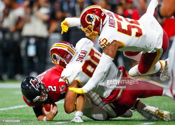 Quarterback Matt Ryan of the Atlanta Falcons is sacked by linebacker Montez Sweat of the Washington Redskins and Ryan Anderson in the first half of...