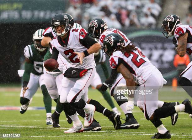 Quarterback Matt Ryan of the Atlanta Falcons looks to hand off the ball to teammate running back Devonta Freeman against the New York Jets during the...