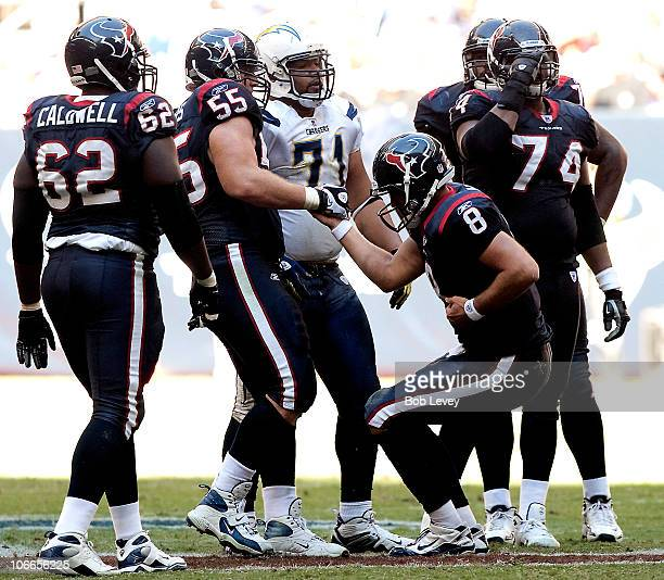 Quarterback Matt Schaub of the Houston Texans holds his side as he is helped up by center Chris Myers after he was sacked by the San Diego...