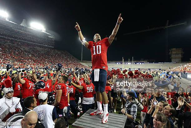 Quarterback Matt Scott of the Arizona Wildcats celebrates with teammates following their 5938 victory over the Oklahoma State Cowboys in the college...