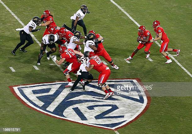 Quarterback Matt Scott of the Arizona Wildcats hands off the football to running back Ka'Deem Carey during the college football game against the...
