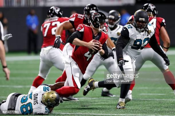 Quarterback Matt Simms of the Atlanta Falcons is tackled by Linebacker PJ Davis of the Jacksonville Jaguars during a preseason game at MercedesBenz...