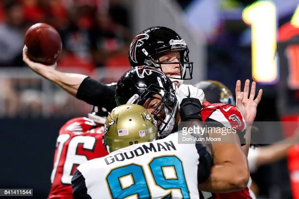 Quarterback Matt Simms of the Atlanta Falcons on a pass play over Defensive End Malliciah Goodman the Jacksonville Jaguars during a preseason game at...