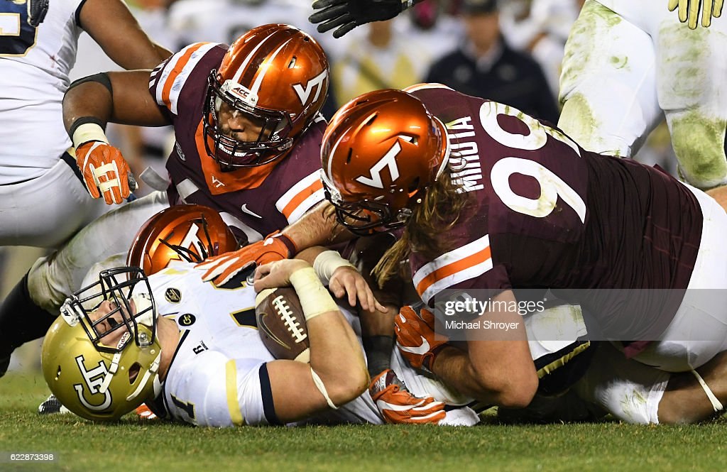 Quarterback Matthew Jordan #11 of the Georgia Tech Yellow Jackets is sacked by defensive lineman Vinny Mihota #99 and defensive tackle Woody Baron #60 of the Virginia Tech Hokies in the second half at Lane Stadium on November 12, 2016 in Blacksburg, Virginia. Georgia Tech defeated Virginia Tech 30-20.