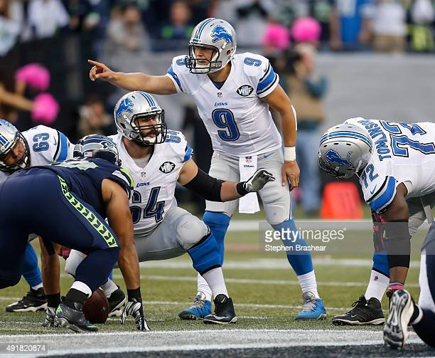 Quarterback Matthew Stafford of the Detroit Lions and center Travis Swanson of the Detroit Lions make signals before a play during a football game...