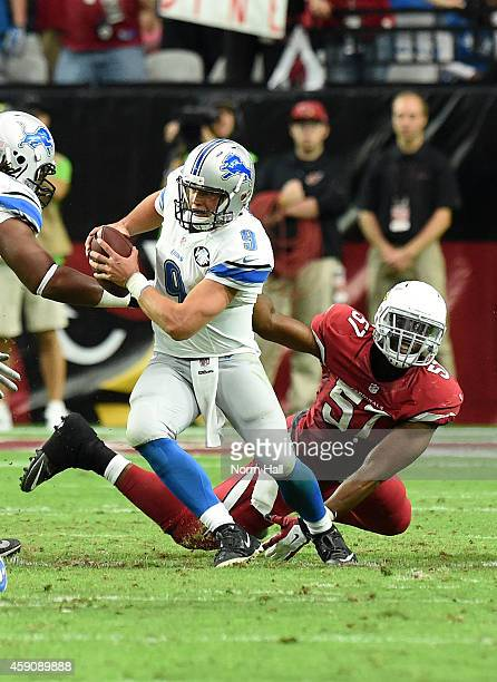 Quarterback Matthew Stafford of the Detroit Lions avoids a tackle by outside linebacker Alex Okafor of the Arizona Cardinals in the fourth quarter at...