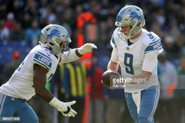 Quarterback Matthew Stafford of the Detroit Lions hands the ball off to running back Theo Riddick in the first quarter against the Baltimore Ravens...