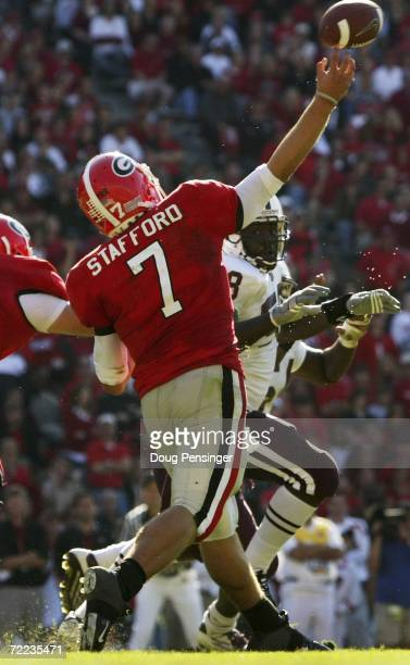 Quarterback Matthew Stafford of the Georgia Bulldogs unleashes a pass as Johnny Carpenter of the Mississippi State Bulldogs defends during SEC...