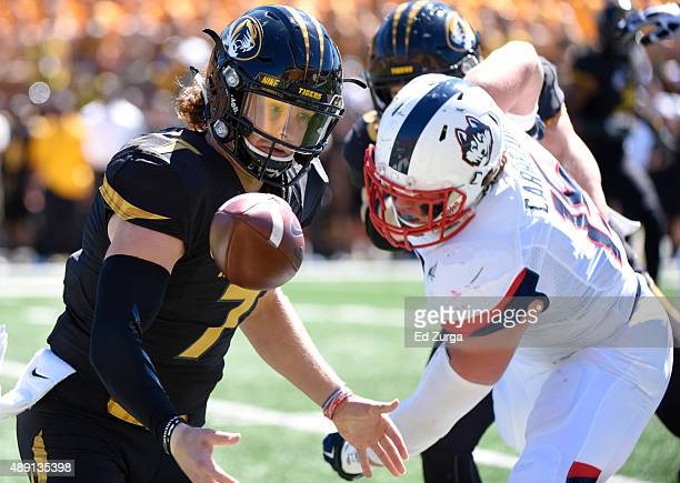 Quarterback Maty Mauk of the Missouri Tigers fumbles the ball as he tries to get past Luke Carrezola of the Connecticut Huskies in the second quarter...