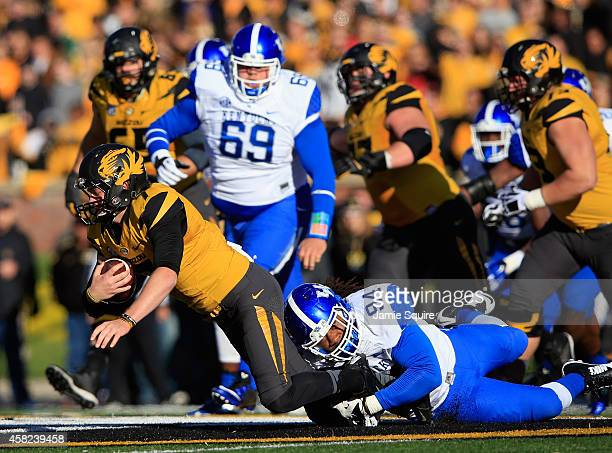 Quarterback Maty Mauk of the Missouri Tigers is tackled by Za'Darius Smith of the Kentucky Wildcats after scramblking during the game at Faurot...
