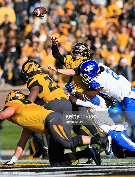 Quarterback Maty Mauk of the Missouri Tigers releases the ball as he is hit by Alvin Dupree of the Kentucky Wildcats during the game at Faurot...