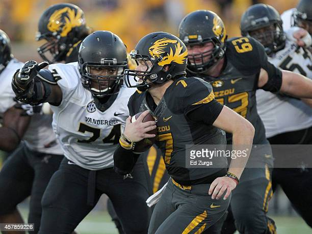 Quarterback Maty Mauk of the Missouri Tigers slips past Jay Woods of the Vanderbilt Commodores as he finds running room in the fourth quarter at...