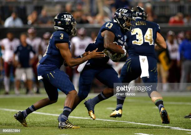 Quarterback Maurice Alexander of the Fiu Golden Panthers hands off to running back Napoleon Maxwell during the first quarter of the Bad Boy Mowers...