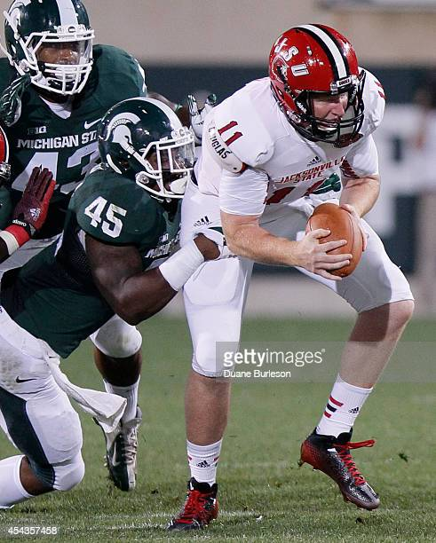 Quarterback Max Shortell of the Jacksonville State Gamecocks is sacked by linebacker Darien Harris of the Michigan State Spartans for an eightyard...