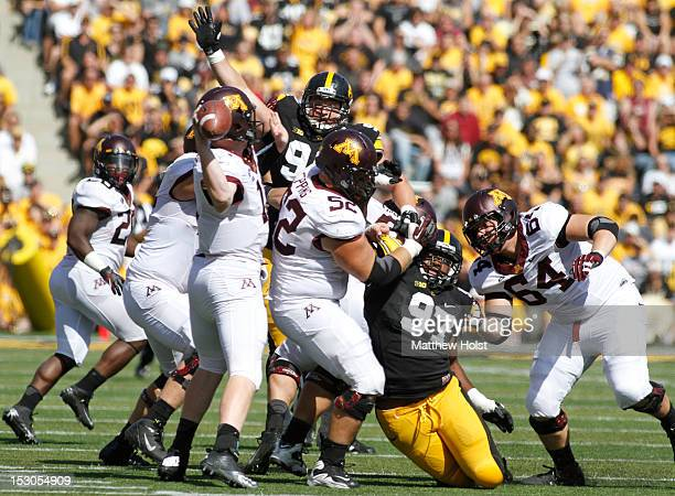 Quarterback Max Shortell of the Minnesota Gophers makes a pass under pressure during the second quarter against defensive lineman Joe Gaglione and...