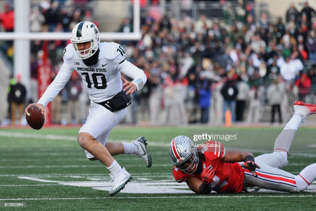 Quarterback Messiah deWeaver #10 of the Michigan State Spartans is tripped up on fourth down by Chase Young #2 of the Ohio State Buckeyes in the fourth quarter at Ohio Stadium on November 11, 2017 in Columbus, Ohio. Ohio State defeated Michigan State 48-3.