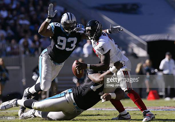 Quarterback Michael Vick of the Atlanta Falcons is brought down by Defensive tackle Kris Jenkins and Defensive end Mike Rucker of the Carolina...