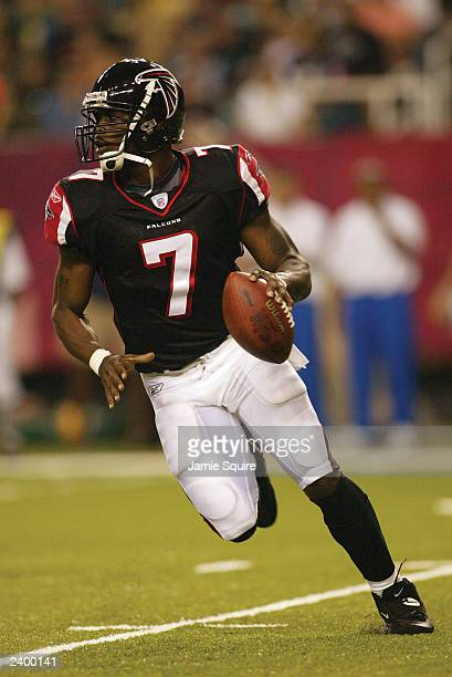 Quarterback Michael Vick of the Atlanta Falcons rolls out against the Green Bay Packers on August 9, 2003 at the Georgia Dome in Atlanta, Georgia....