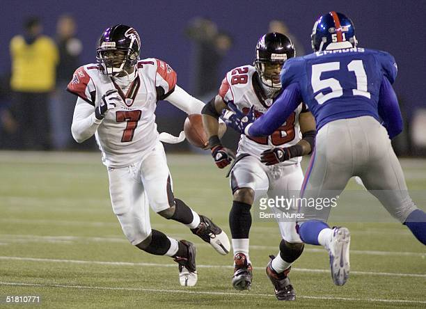 Quarterback Michael Vick of the Atlanta Falcons runs behind the block of running back Warrick Dunn against linebacker Carlos Emmons of the New York...