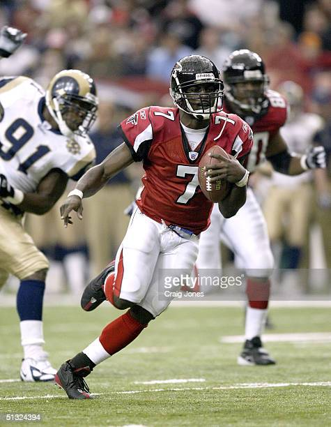 Quarterback Michael Vick of the Atlanta Falcons runs by Leonard Little of the St. Louis Rams on September 19, 2004 at the Georgia Dome in Atlanta,...