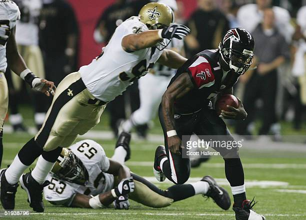 Quarterback Michael Vick of the Atlanta Falcons scrambles during the game against the New Orleans Saints at the Georgia Dome on November 28, 2004 in...