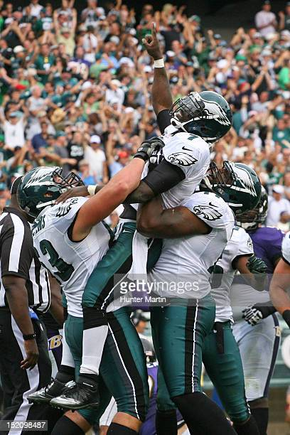 Quarterback Michael Vick of the Philadelphia Eagles celebrates scoring a touchdown with guard Danny Watkins and tackle Demetress Bell during a game...