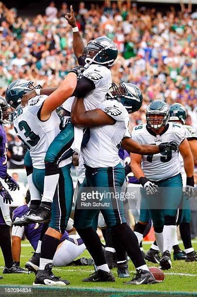Quarterback Michael Vick of the Philadelphia Eagles is lifted by teammates Danny Watkins and Demetress Bell after Vick ran for a six yard touchdown...
