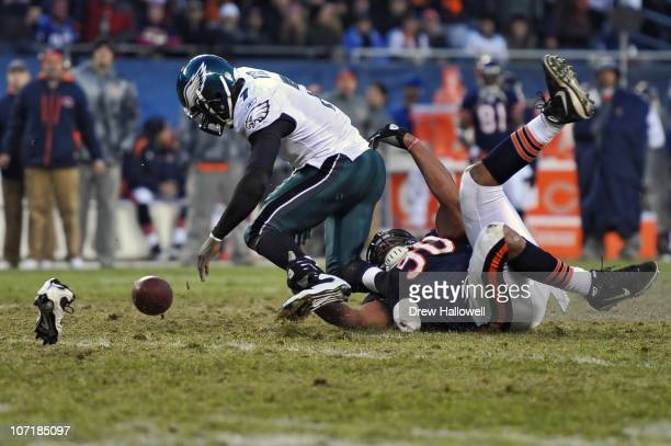 Quarterback Michael Vick of the Philadelphia Eagles loses his shoe and the ball while being sacked by defensive end Julius Peppers of the Chicago...