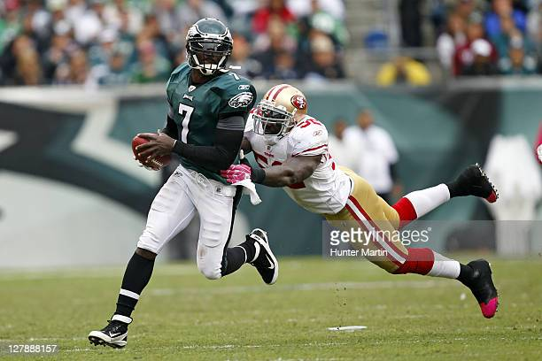 Quarterback Michael Vick of the Philadelphia Eagles runs with the ball as inside linebacker Patrick Willis of the San Francisco 49ers attempts to...