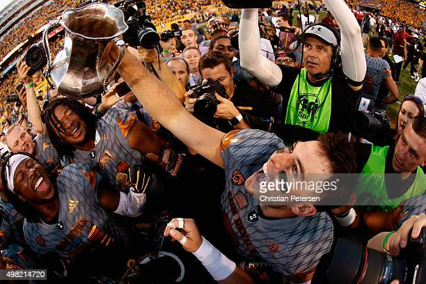 Quarterback Mike Bercovici of the Arizona State Sun Devils celebrates with the Territorial Cup after defeating the Arizona Wildcats 5237 in the...
