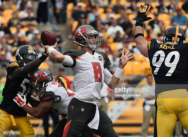 Quarterback Mike Glennon of the Tampa Bay Buccaneers passes while under pressure from linebacker Sean Spence and defensive lineman Brett Keisel of...