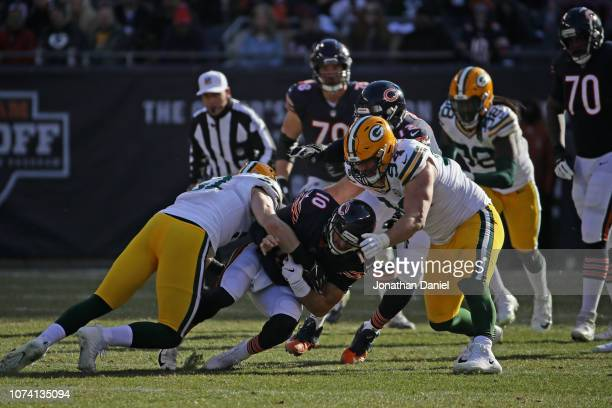 Quarterback Mitchell Trubisky of the Chicago Bears carries the football against Kyler Fackrell and Dean Lowry of the Green Bay Packers in the second...