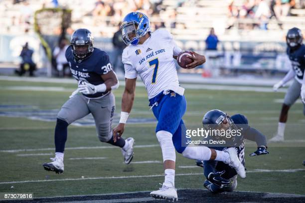 Quarterback Montel Aaron of the San Jose State Spartans tries to get around the Nevada Wolf Pack defense at Mackay Stadium on November 11 2017 in...