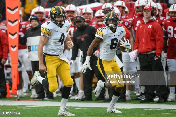 Quarterback Nate Stanley of the Iowa Hawkeyes leads the way for wide receiver Ihmir SmithMarsette to score against the Nebraska Cornhuskers at...