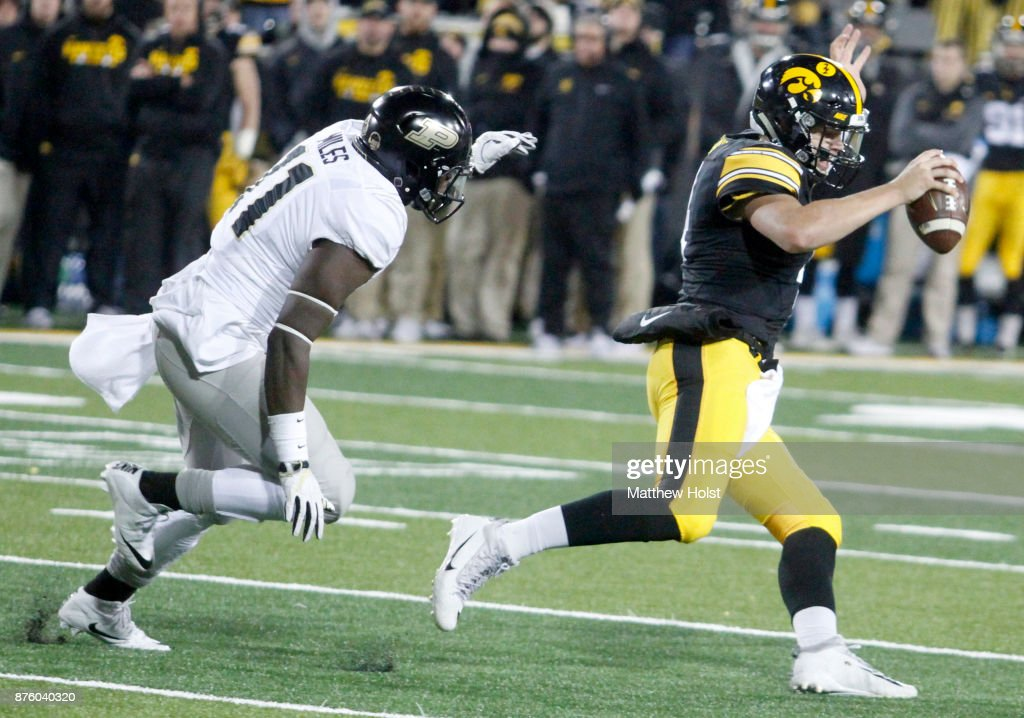 Quarterback Nate Stanley #4 of the Iowa Hawkeyes scrambles on a keeper during the fourth quarter in front of defensive end Antoine Miles #11 of the Purdue Boilermakers on November 18, 2017 at Kinnick Stadium in Iowa City, Iowa.