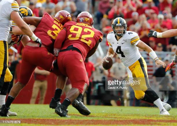 Quarterback Nate Stanley of the Iowa Hawkeyes scrambles under pressure from defensive end JaQuan Bailey, and defensive lineman Jamahl Johnson of the...