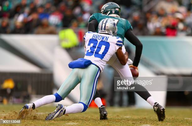 Quarterback Nate Sudfeld of the Philadelphia Eagles is sacked by cornerback Anthony Brown of the Dallas Cowboys during the second half of the game at...