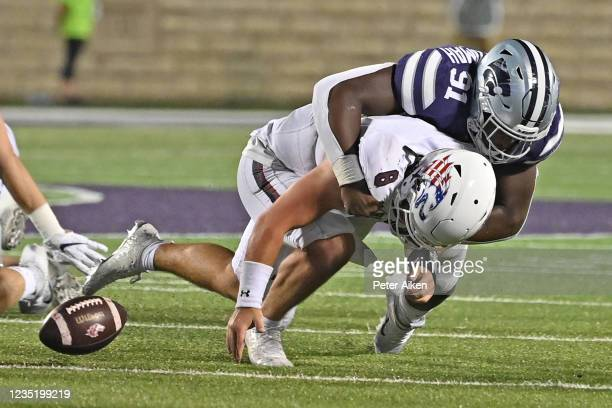 Quarterback Nic Baker of the Southern Illinois Salukis fumbles the ball after getting hit by defensive end Felix Anudike of the Kansas State Wildcats...