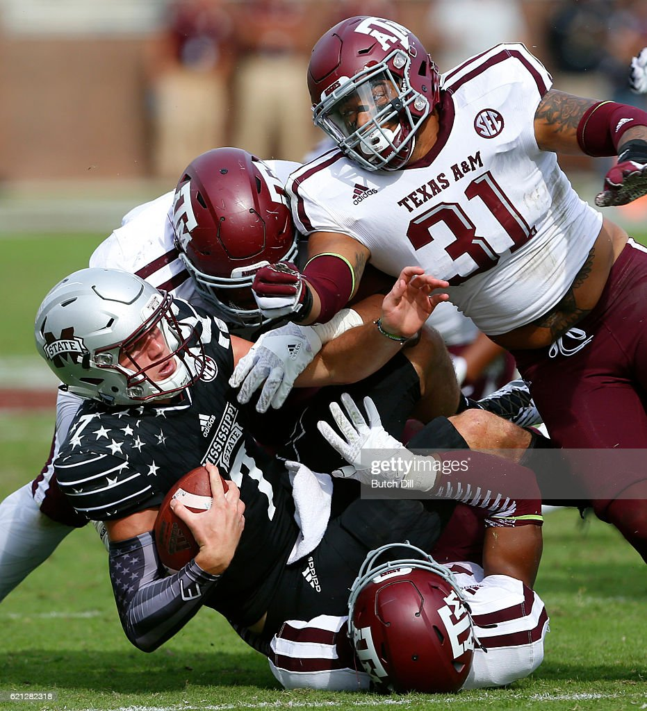 Quarterback Nick Fitzgerald #7 of the Mississippi State Bulldogs is tackled by linebacker Claude George #31, defensive lineman Kingsley Keke #88, and defensive back DeShawn Capers-Smith #26 of the Texas A&M Aggies during the second half of an NCAA college football game at Davis Wade Stadium on November 5, 2016 in Starkville, Mississippi.