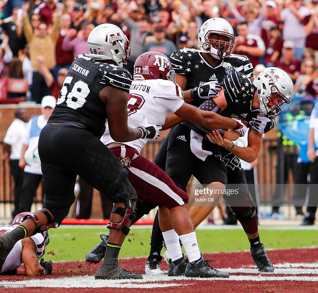 Quarterback Nick Fitzgerald #7 of the Mississippi State Bulldogs plows his way into the end zone for a touchdown as linebacker Shaan Washington #33 of the Texas A&M Aggies tries to strip the ball during the second half of an NCAA college football game at Davis Wade Stadium on November 5, 2016 in Starkville, Mississippi.