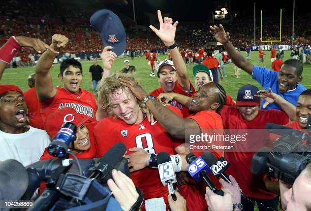Quarterback Nick Foles of the Arizona Wildcats celebrates with fans and players after defeating the Iowa Hawkeyes in the college football game at...