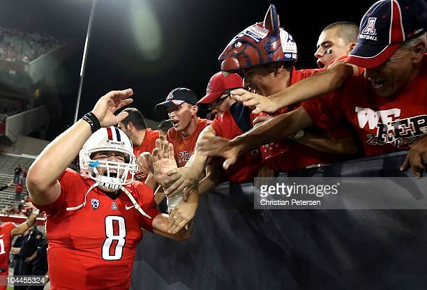 Quarterback Nick Foles of the Arizona Wildcats celebrates with fans after defeating the California Golden Bears in the college football game at...