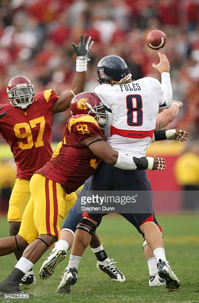 Quarterback Nick Foles of the Arizona Wildcats is hit as he throws a pass by defensive end Everson Griffen of the USC Trojans on December 5 2009 at...
