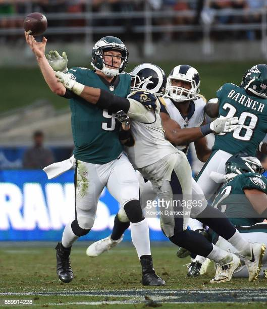 Quarterback Nick Foles of the Philadelphia Eagles throws a pass under pressure from tight end Tyler Higbee of the Los Angeles Rams during the fourth...