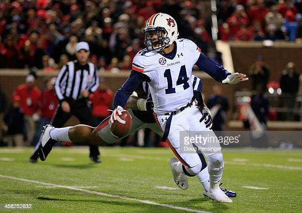 Quarterback Nick Marshall of the Auburn Tigers eludes Robert Nkemdiche of the Mississippi Rebels and completes a first down pass in the third quarter...