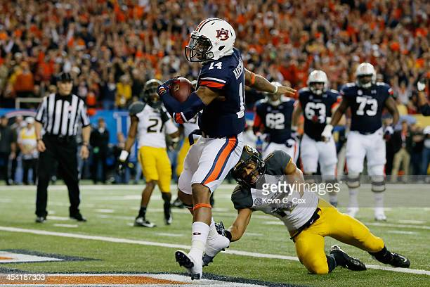 Quarterback Nick Marshall of the Auburn Tigers scores a touchdown in the first quarter against Matt White of the Missouri Tigers during the SEC...
